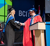 faculty shaking graduate's hand