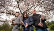 Instructor and two biotech students in front of cherry trees