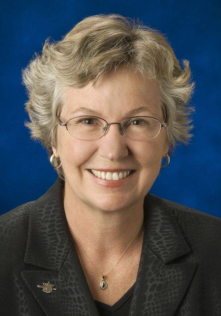 Photo of Kathy Corrigan wearing glasses smiling at the camera.