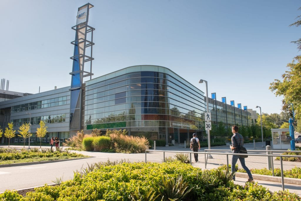 Burnaby campus SW01 building with 2 students walking towards it and 2 students standing outside of it..