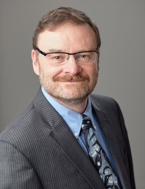 head and chest photo of a man with beard and glasses and short light brownish red hair wearing business attire.
