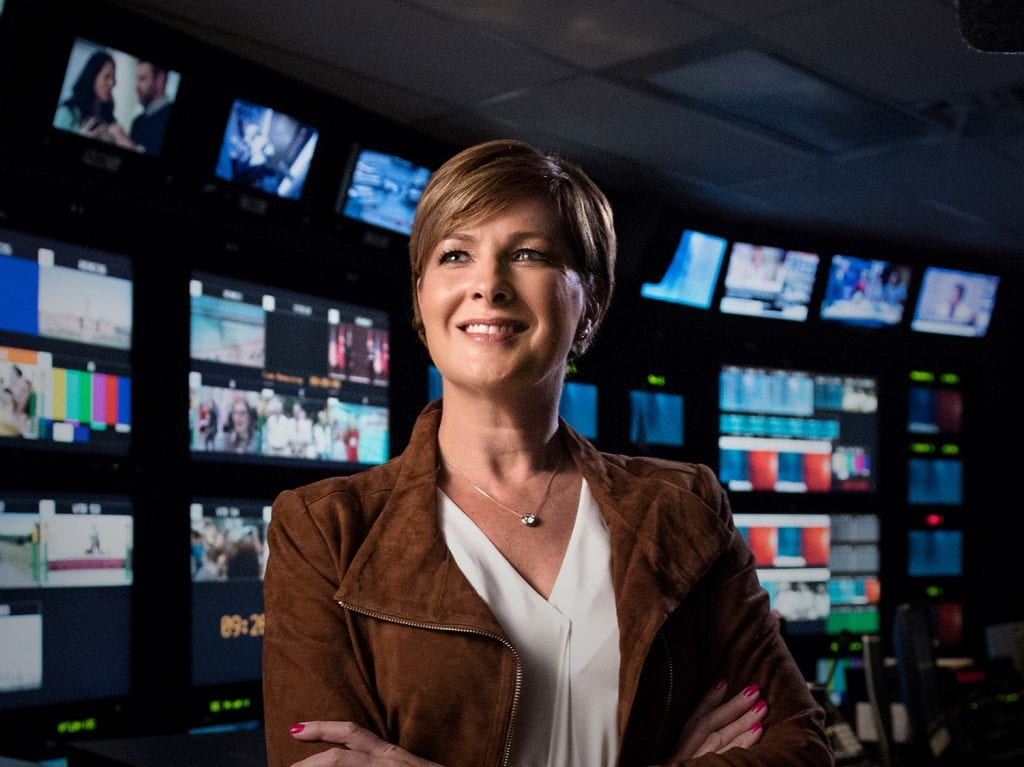 Diana Swain standing in a news broadcasting room.
