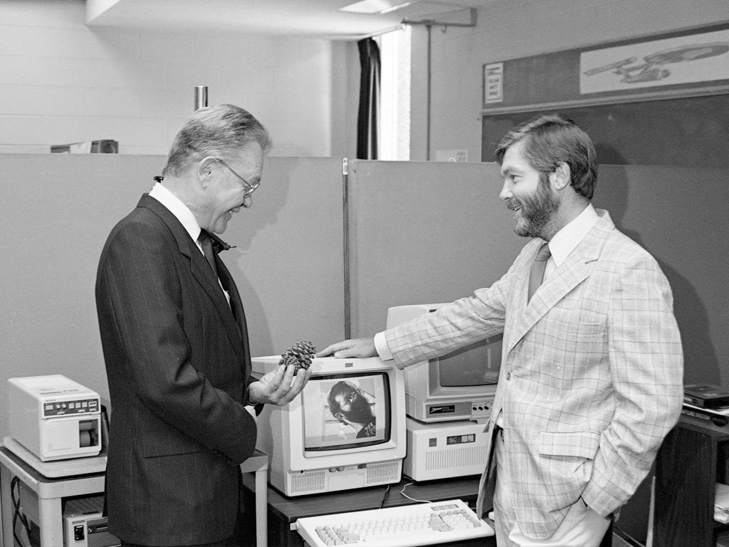 Two researchers beside old computer