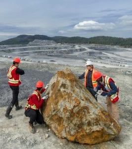 Mineral Exploration and Mining Technology students and their instructor examine the geology of a boulder at the Lafarge Texada Quarry on Texada Island, BC.