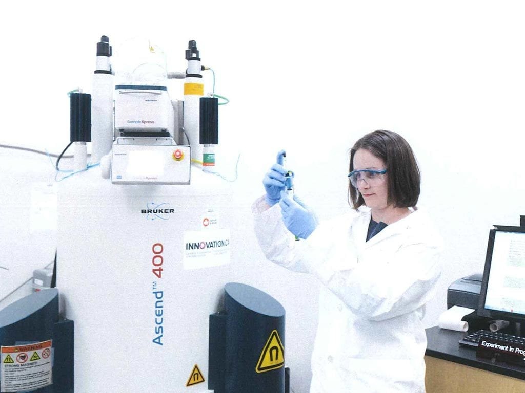 Female scientist beside Nuclear Magnetic Resonance spectrometer.