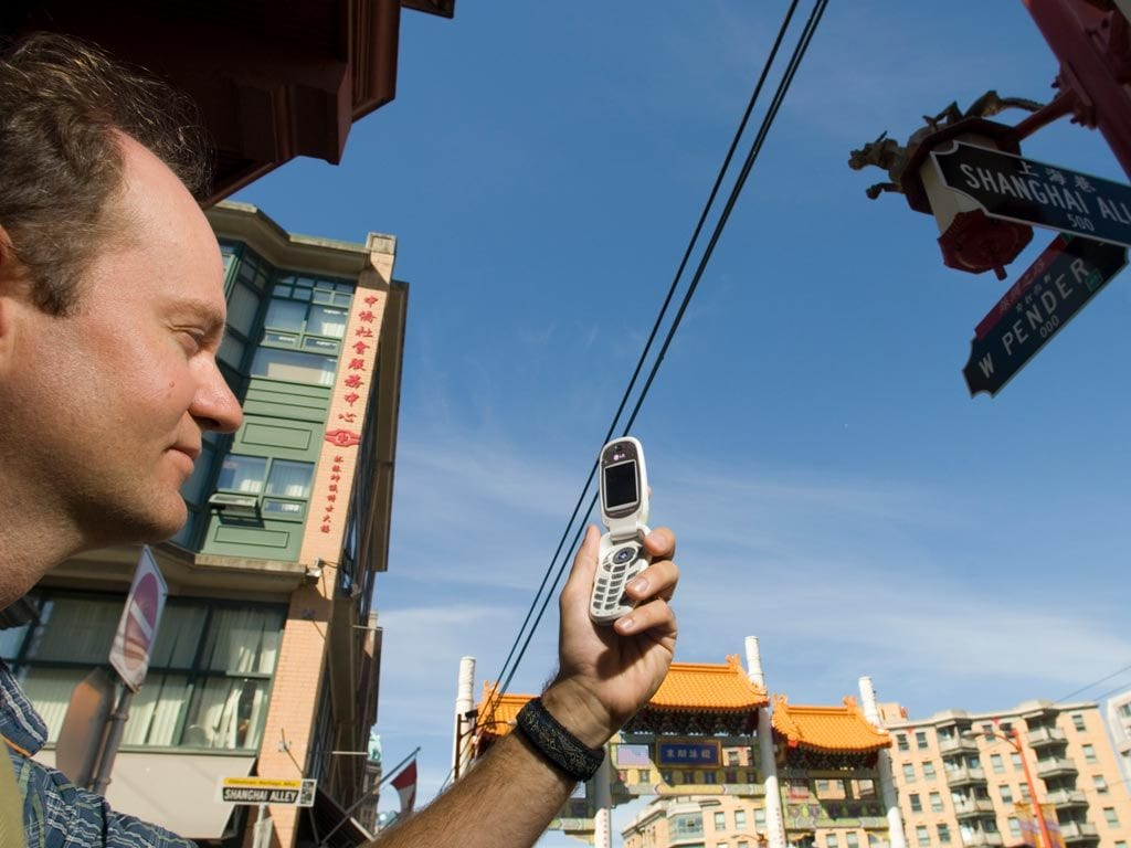 Man hlds looks at cellphone screen outside with buildingings and utility wires running