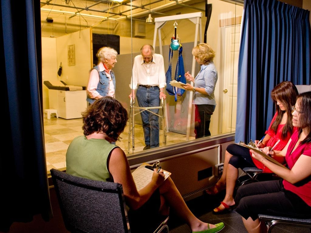 Three female researchers watch three older individuals in a lab from behind a oneway mirror.