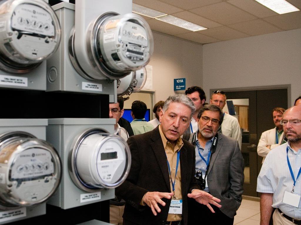 Four men in a room looking at smart meters
