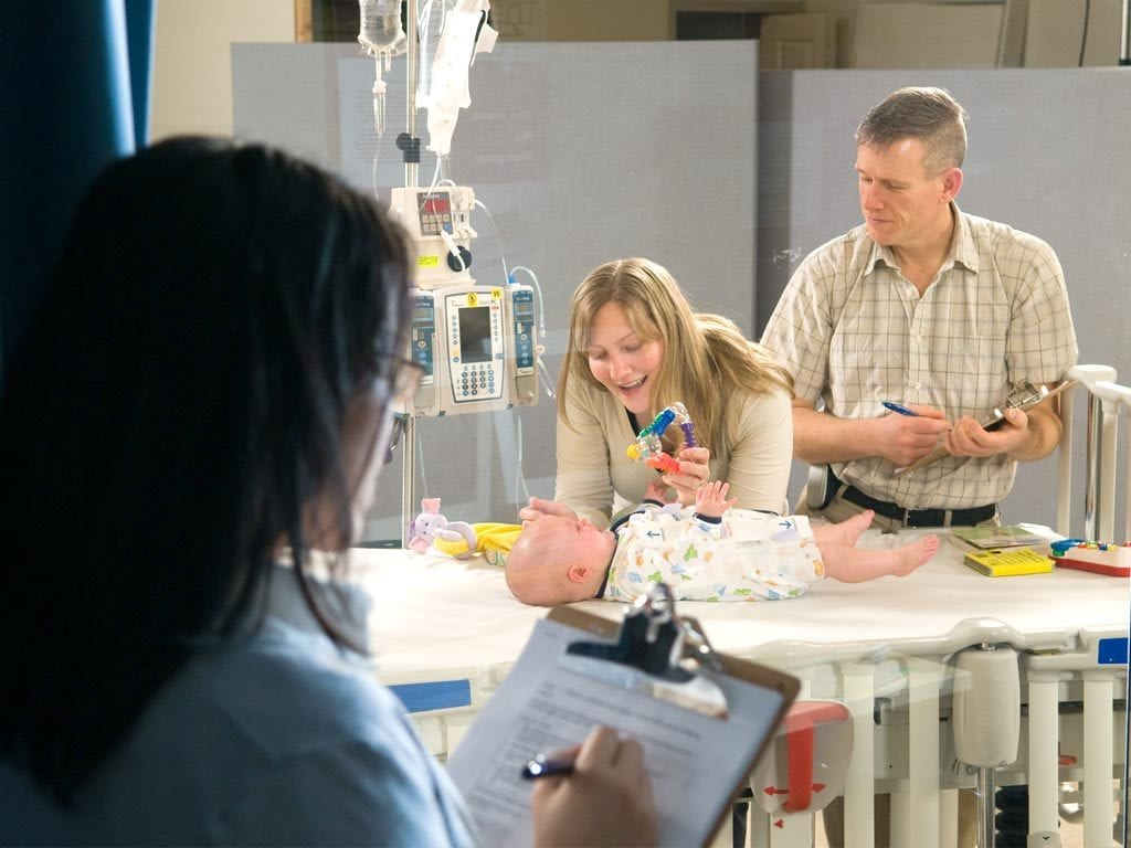 Researcher behind one-sided glass watches woman with baby lying on hospital bed.