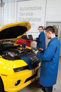 two students in blue lab coats performing diagnostic testing on a yellow automobile in a mechanical shop.