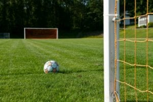 Lawn covered soccer field with two goal nets on each end with a white and orange soccer ball in front of one net.