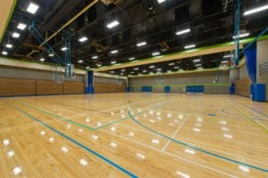 Looking from the entrance there is an empty gymnasium that is well lit with a shiny wood floor with various sport layout markings on the floor.