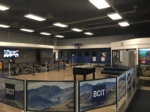 The main lobby of the BCIT Recreation Centre is a classroom size with exercise bikes and equipment along one wall, a foozeball table in centre with seating and is bordered by waist high screens with picturesque mountains and BCIT logo on blue background.