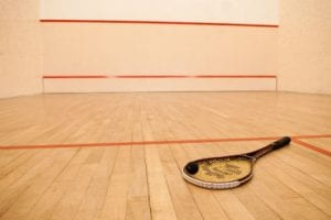 Squash court with beige colored hardwood floor and in the foreground there is a squash racquet with a black ball on the strings.