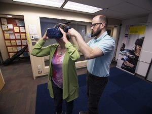 two people first person wearing lime green sweater over pink and white top and black pants and second person semi bald man wearing glasses light brown beard and mustache wearing a light blue shirt and black pants in a virtual reality room performing a simulation.