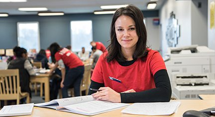 Female tutor seated at a desk wearing red shirt and has shoulder length brown hair.