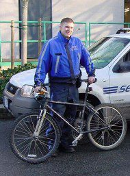 Security man wearing blue uniform holding a mountain bike.
