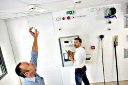 one technician reaching up towards the ceiling in a room and the other technician working at a control panel while looking at the other person.