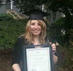 Female graduate in cap and gown holding framed diploma.