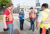 Disaster personnel listening to a person giving direction.