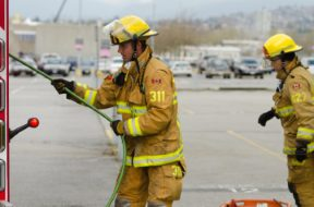 Two firemen dressed in yellow suits work with equipment.