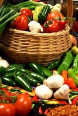 Image of a basket of tomatoes, green and yellow pepers, green onions and garlic.