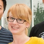 headshot of a young female with black rimmed square glasses, long reddish blond bangs and yellow shirt.