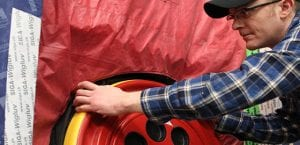 Male construction tradesperson with glasses in plaid shirt and baseball cap using a blower door tester.