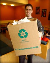 Photo of a student holding a large, light brown recycling box that has a green recycling arrows logo on the front of it with white paper sticking up out of the box.