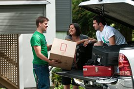 Photo of three students standing outside a truck and one student is holding a small, square box.