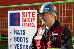 A safety officer at the Site Safety Apparel sign.