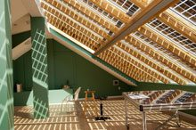 attic open design skylight panels casting grid like shadows on room with green walls.