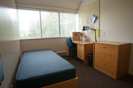 Image of an on-campus housing room with a bed, dresser, desk, chair and desk lamp.