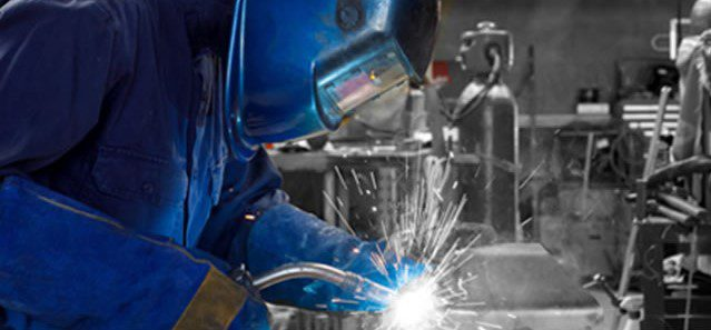 side view of a person in blue garb and helmet welding an item in front.