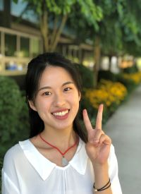 student life ambassador with long dark hair showing peace sign