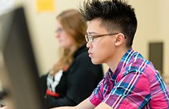 asian man with glasses and short spiky hair working at a computer station.