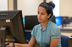 lady with black hair and pony tail working at a computer in a lab.