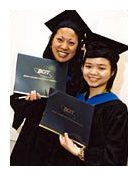 Two students wearing black graduation caps and gowns holding black diplomas.