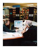 Two people sitting at a table in the library looking at a computer monitor.