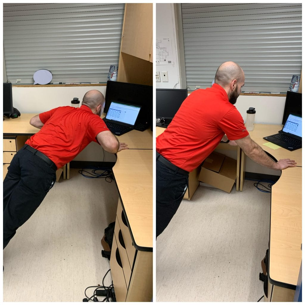 man doing an incline pushup be leaning on a desk