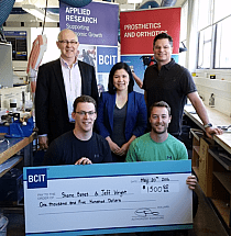 Photo of jeff wright and shane bates kneeling down, holding a cheque for 1,500 dollars and three people standing behind them.