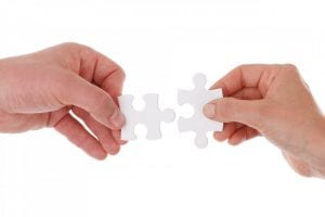 two hands, each holding a puzzle piece that will fit the other