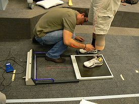 Person squatting and measuring a foot in the motion capture lab.