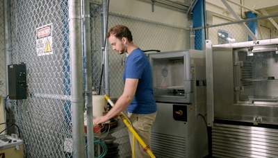Medium image of person wearing a blue shirt and tan pants in the medium voltage testing lab at bcit.