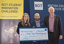 Photo of two students holding a cheque and another person standing beside them.