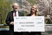 Photo of nicola gardner and another person holding a cheque for 5,000 dollars.