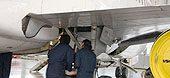 technicians working on underside of an aircraft.