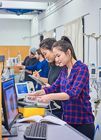Photo of four students in biomedical engineering and one student is testing a defibrillator machine.