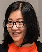 Carly Orr Head shot smiling with black hair and glasses.