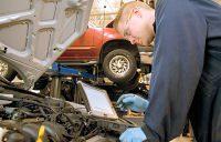 mechanic running diagnostics on a vehicle engine.